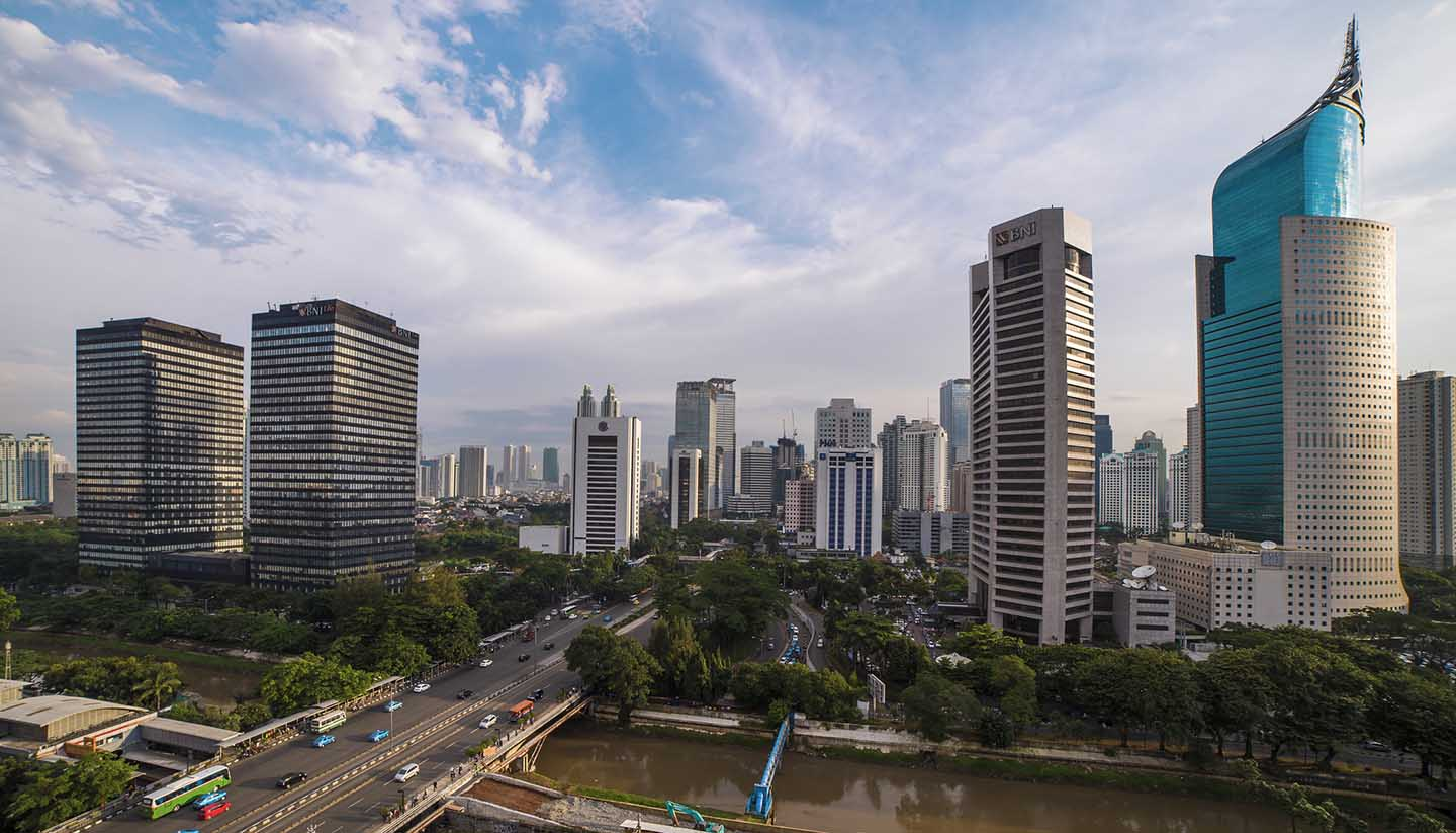 Panorama of Jakarta Skyline with blue sky and no traffic. BNI46 Building from left to right
